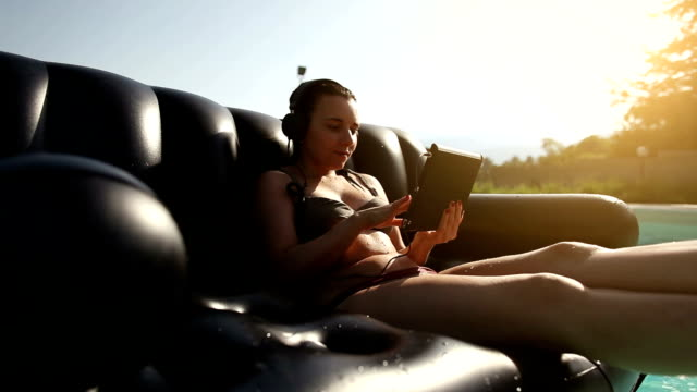 Girl at the swimming pool with digital tablet