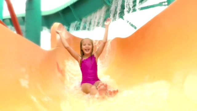 Girl at water park sliding down giant water slide