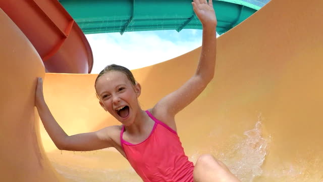 Girl at water park sliding down waterslide