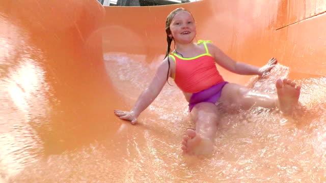 vídeos de stock, filmes e b-roll de garota no parque aquático descendo toboágua - roupa de natação