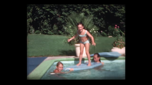 vídeos y material grabado en eventos de stock de 1967 girl balances on surf board in family pool - tabla de surf