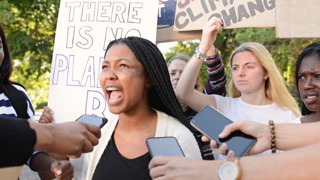 vídeos y material grabado en eventos de stock de chica siendo entrevistada por los medios durante una protesta contra el cambio climático - journalist