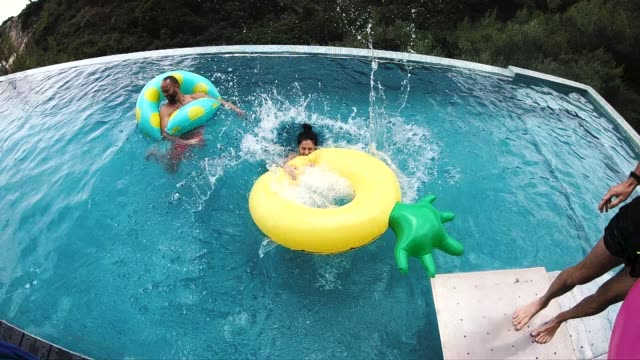 girl being pushed into the swimming pool - inner tube stock videos and b-roll footage