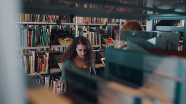 girl between bookshelves - library stock videos and b-roll footage