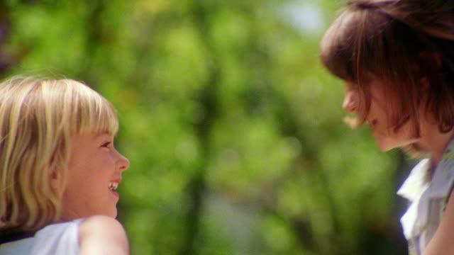 vidéos et rushes de ms girl + blonde girl holding hands + spinning on grass laughing / zoom in portrait girls hugging - children only