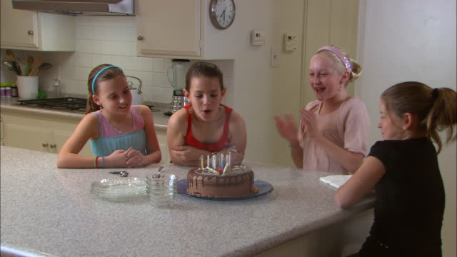 ms, girl (10-11) blowing birthday candles on cake, three friends clapping - 10 11 jahre stock-videos und b-roll-filmmaterial