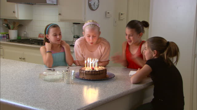 MS, Girl (10-11) blowing birthday candles on cake, three friends clapping