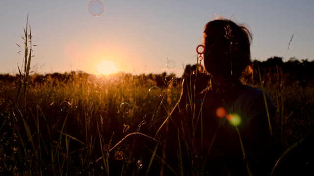 SLO MO Girl Blowing Bubbles At Sunset