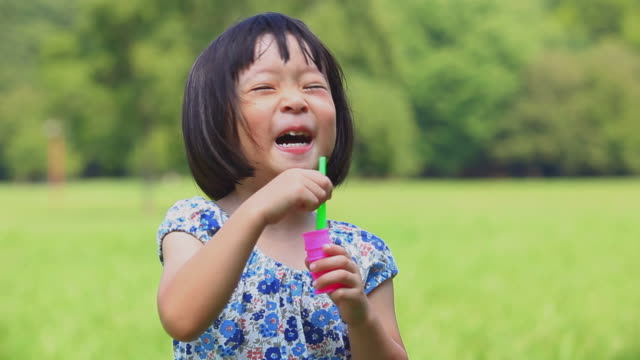 ms girl (4-5) blowing bubbles in park / koganei, tokyo, japan - 子供時代点の映像素材/bロール