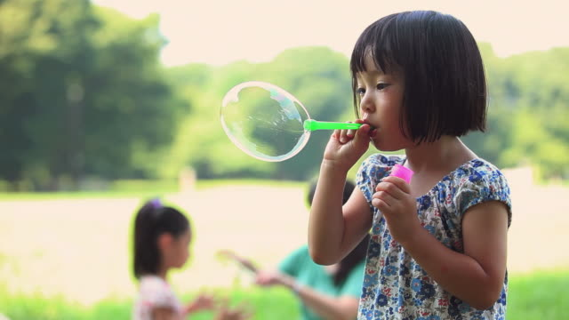 ms girl (4-5) blowing bubbles in park / koganei, tokyo, japan - bubble wand stock videos & royalty-free footage