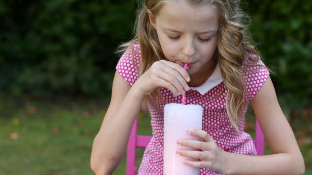 girl blowing bubbles in pink milkshake - milk stock videos & royalty-free footage