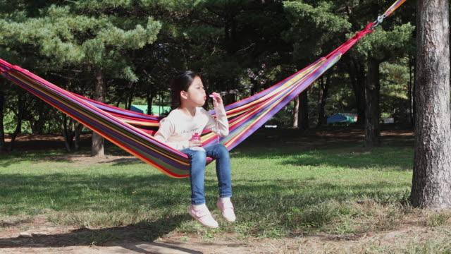a girl blowing bubbles in the hammock - östasien bildbanksvideor och videomaterial från bakom kulisserna