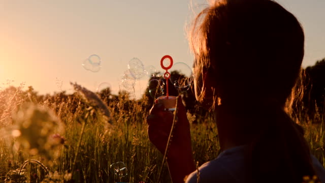 slo mo girl blowing bubbles - bubble wand stock videos & royalty-free footage