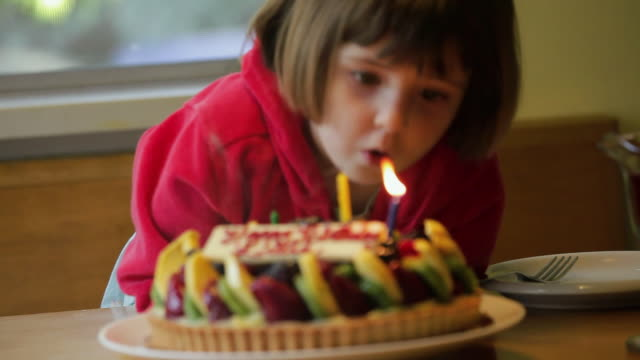 CU FOCUSING Girl (2-3) blowing candles on birthday cake, Los Angeles, California, USA
