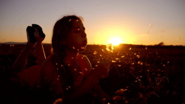 SLO MO Mädchen Blasen Löwenzahn bei Sonnenuntergang