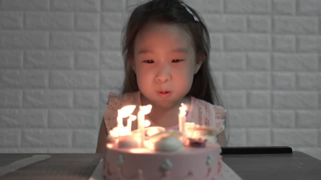 girl blowing out candles on a birthday cake on her birthday - birthday gift stock videos & royalty-free footage