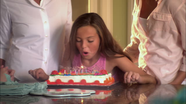 CU Girl (10-11) blowing out self igniting candles on birthday cake in dining room / Jacksonville, Florida, USA