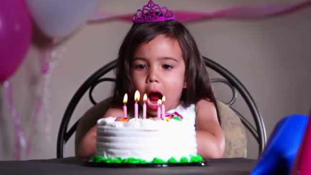 vídeos de stock, filmes e b-roll de menina sopra out velas de aniversário em um bolo de - artigo de vestuário para cabeça