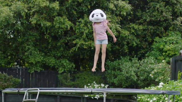 girl bouncing on trampoline in panda mask - rimbalzare video stock e b–roll