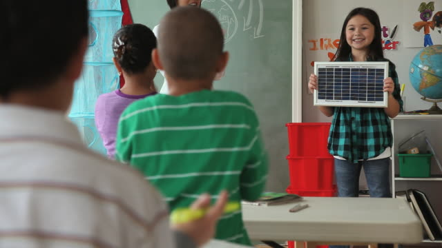 MS SELECTIVE FOCUS Girl (6-7) bowing after giving solar panel presentation in class / Jersey City, New Jersey State, USA