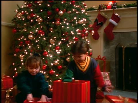 girl + boy opening christmas gifts + hugging doll + teddy bear near christmas tree in living room - teddy boy stock videos & royalty-free footage