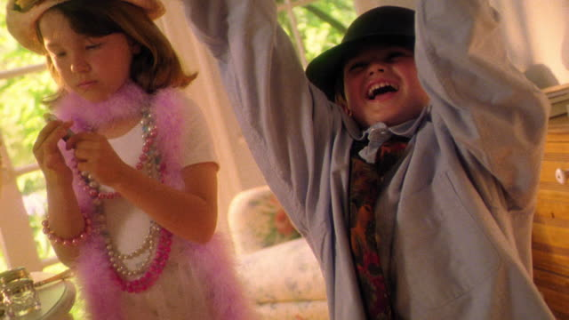 Girl + boy play dress-up / boy in hat + huge shirt laughing + pulling sleeves down to reveal hands