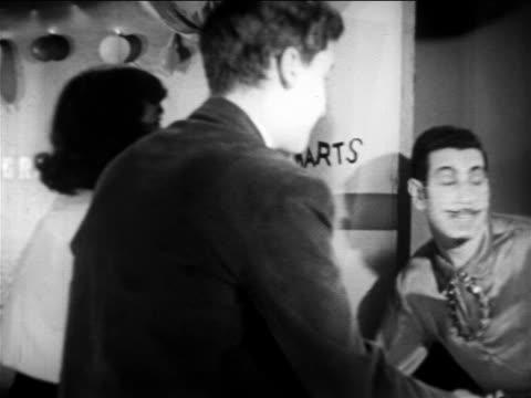 b/w 1949 rear view girl + boy throwing darts at something offscreen / educational - 1949 stock-videos und b-roll-filmmaterial