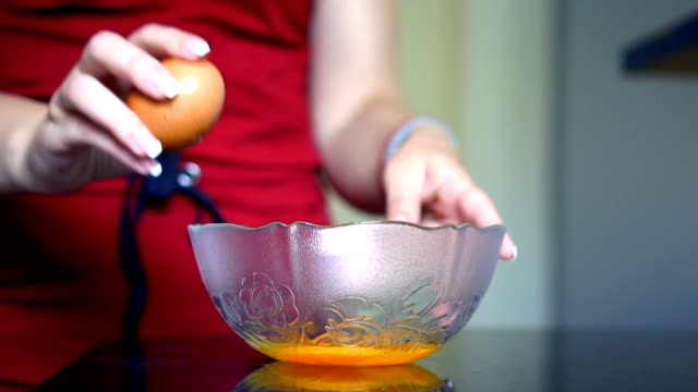 slow mo - girl breaks eggs  for breakfast - baking stock videos & royalty-free footage