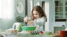 Girl breaks the eggs into a bowl