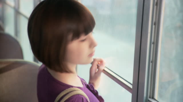 girl breathing on bus window and drawing in condensation - 景色を眺める点の映像素材/bロール
