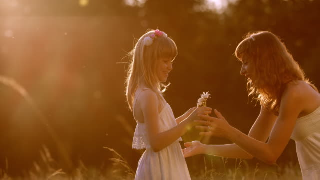 slo mo girl bringing flowers to mother at sunset - giving stock videos & royalty-free footage