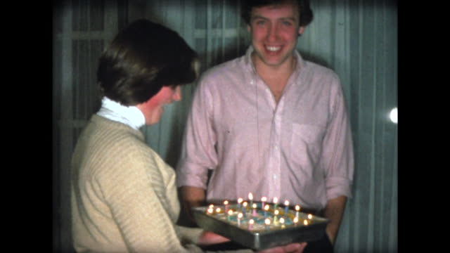 1976 girl brings out birthday cake with candles for brother - birthday stock videos & royalty-free footage