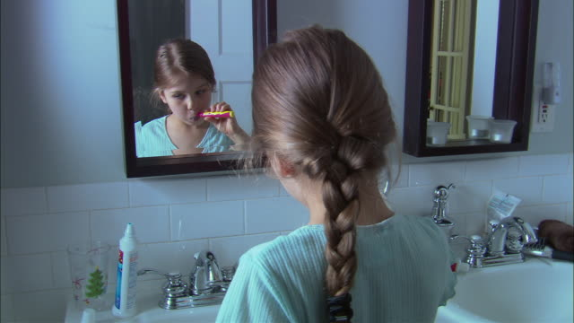 cu girl brushing her teeth in front of bathroom mirror, then drinks water and smiles / westfield, new jersey, usa - toothpaste stock videos & royalty-free footage