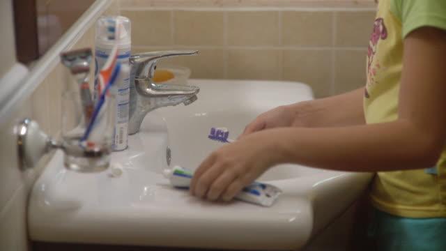 cu tu girl (10-11) brushing teeth in bathroom / havana, cuba - toothpaste stock videos and b-roll footage