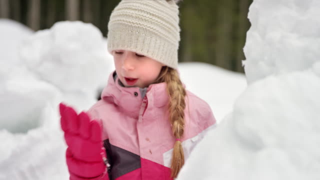 slo mo girl building a snowman - hat stock videos & royalty-free footage