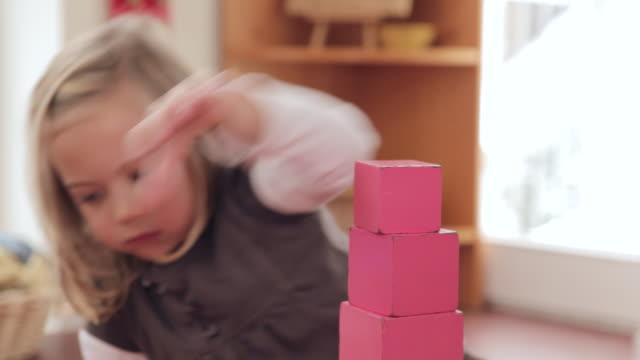 ms girl building up pink tower / potsdam, brandenburg, germany - gestapelt stock-videos und b-roll-filmmaterial