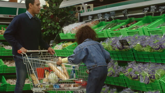Girl buying fresh produce with dad in supermarket