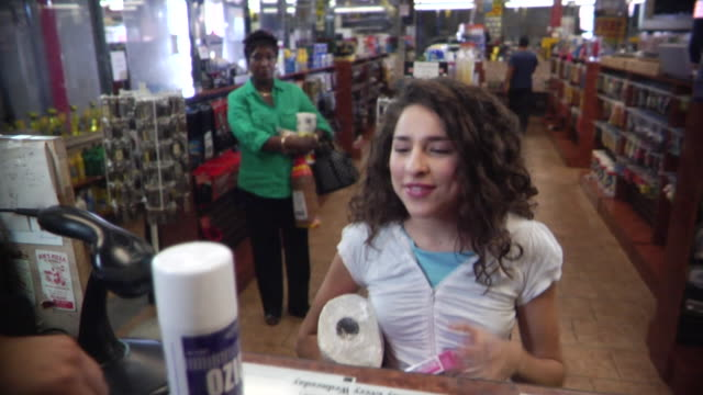 vídeos de stock, filmes e b-roll de ms girl buying items at convenience store counter while another customer waits in line behind her / brooklyn, new york, usa - loja de conveniência