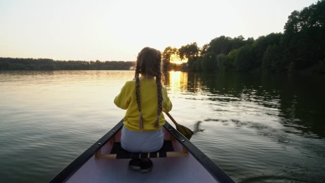 vídeos de stock e filmes b-roll de girl canoeing on lake at sunset - kayaking