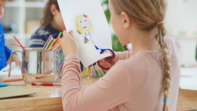 girl carefully cutting out her drawing of a little girl - scissors stock videos & royalty-free footage