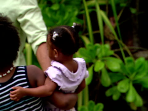 stockvideo's en b-roll-footage met zo,  ms,  girl carrying baby sister,  posing for portrait with parents,  harbour island,  bahamas,  cu - haaraccessoires