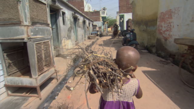 ms pov girl carrying bundle of sticks down street, districts of delhi, india - slum stock videos & royalty-free footage