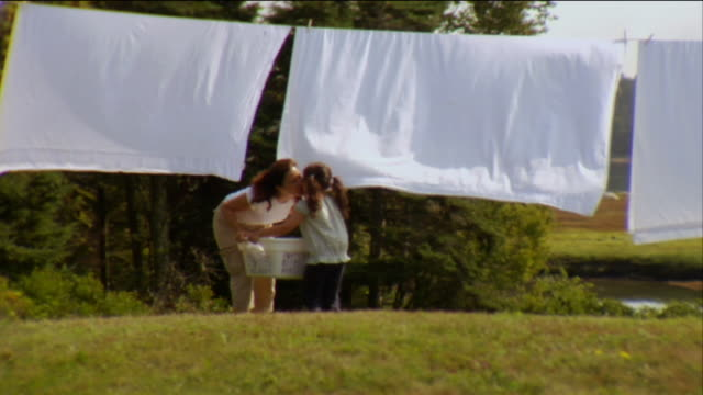 sm ws girl carrying laundry basket to mother as she hangs sheets on clothes line / vinalhaven, maine, usa - carrying stock videos & royalty-free footage