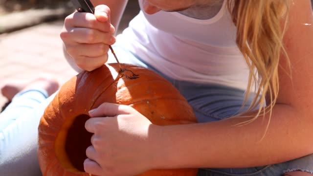 girl carving pumpkin outdoors - pumpkin stock videos & royalty-free footage
