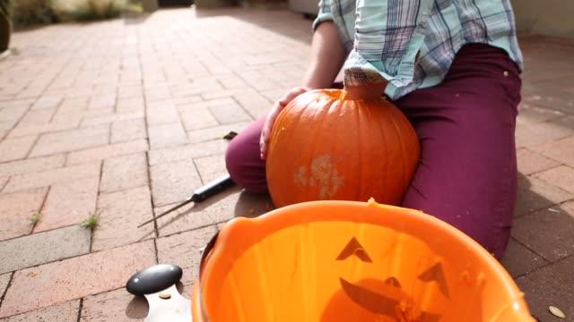 girl carving pumpkin - タータンチェック点の映像素材/bロール