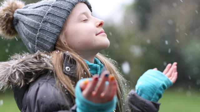 Girl catching falling winter snowflakes