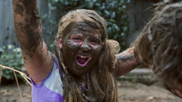 girl celebrating her mud face - cu coverage - schlamm stock-videos und b-roll-filmmaterial