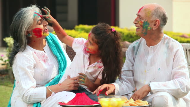 girl celebrating holi festival with her grandparents - active seniors stock videos & royalty-free footage