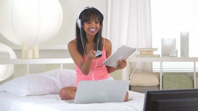 girl changing channel while using tablet and laptop computer