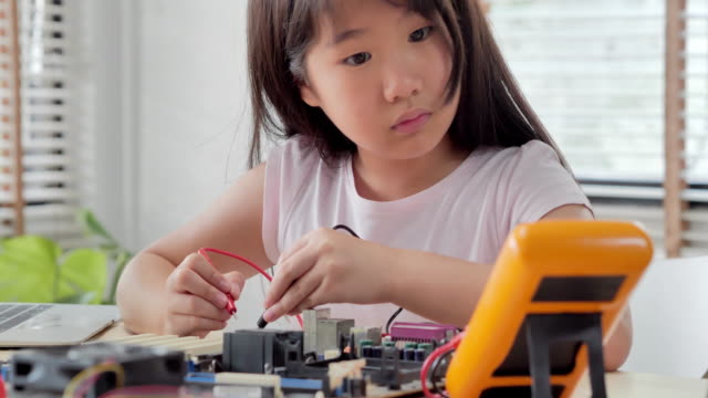 girl checking circuit board with multimeter at home and building a robot as a school science project.she is very satisfied with her work.happy smiling girl constructs technical.education, children, technology, science people concept - genius stock videos & royalty-free footage